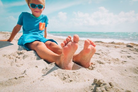 little boy relax at summer beach, focus on feet Stockfoto