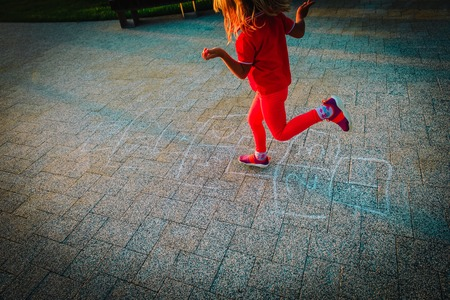 little girl playing hopscotch on playground, outdoor activities