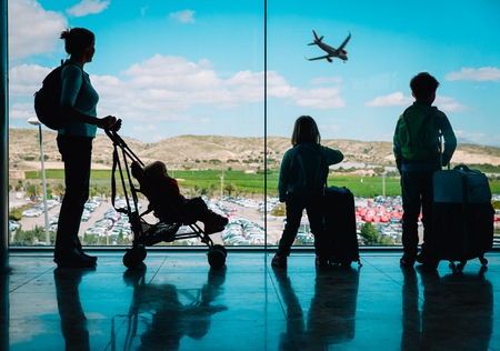 mother with kids and luggage looking at planes in airport Фото со стока
