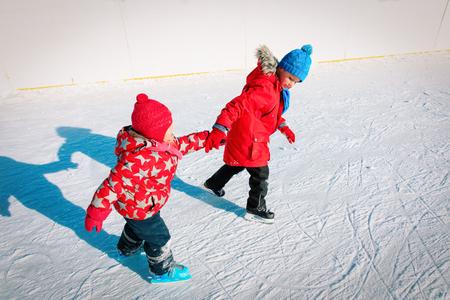 little boy and girl skating together, kids winter sport Banco de Imagens