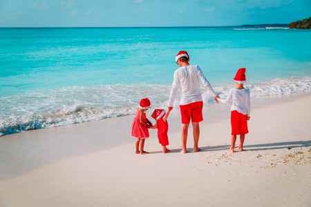 Happy father with kids on beach at Christmas