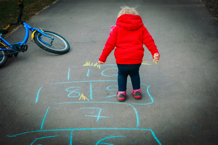 little girl play hopscotch on playground outdoors