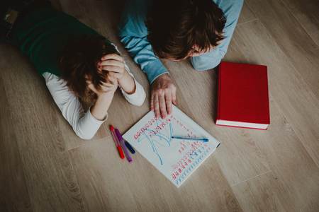 father and son stressed tired of doing homework together Stock Photo