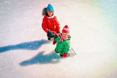 brother teaching little sister to skate in winter Banco de Imagens - 107951587