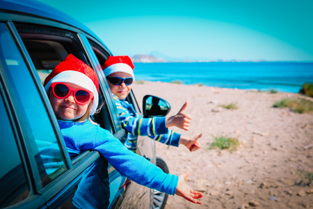 christmas car travel- happy kids travel in winter on beach Stock Photo