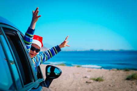 christmas car travel- happy little boy travel in winter on beach