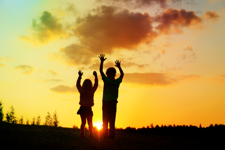 happy boy and girl silhouettes enjoy sunset nature Stock Photo - 107951964