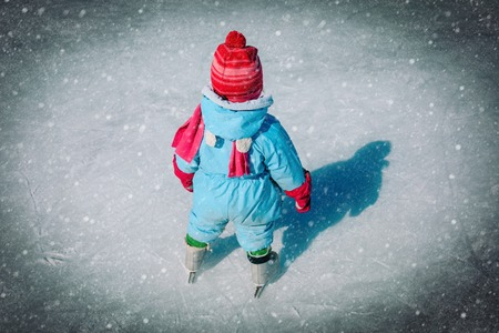 little baby girl learning to skate on ice in winter snow