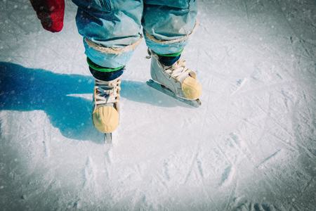 baby learning to skate on ice in winter snow Banco de Imagens - 108177513