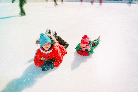 little boy and girl learn to skate in winter