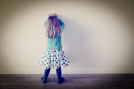 Little girl standing up against a wall Foto de archivo - 108363778