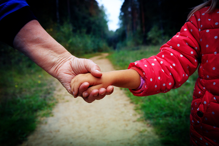 grandmother holding grandchild hand in nature