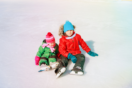 happy kids- boy and girl learning to skate in winter