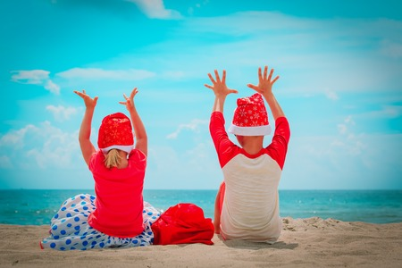 happy kids- little boy and girl- celebrating christmas on tropical beach