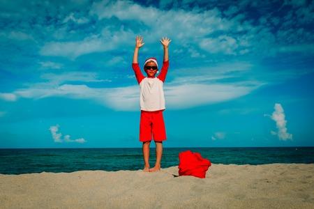 happy little boy celebrating christmas on tropical beach