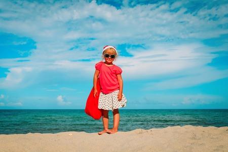 cute happy little girl celebrating christmas on tropical beach