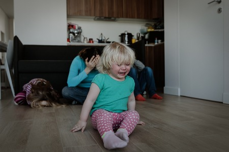 difficult parenting- crying kids and tired mother Stock Photo