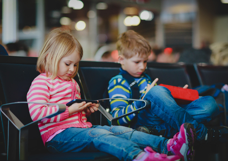 boy and girl looking at touch pad and mobile phone in airport Фото со стока