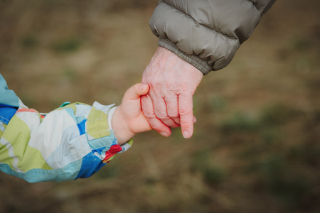 grandmother holding grandchild hand in nature, parenting