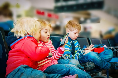 kids - looking at touch pad and mobile phone in airport