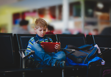 young boy looking at touch pad in the airport