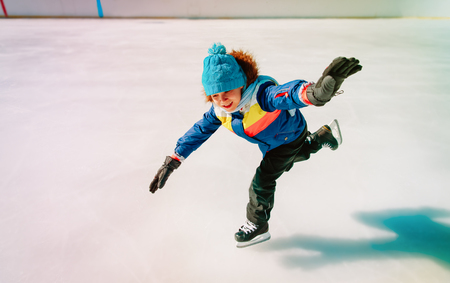 little boy skating on ice in winter nature Stock Photo