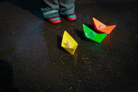 Niño jugando con barcos de papel en charco de agua Foto de archivo - 109087011