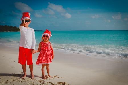 kids- boy and girl- celebrating christmas on tropical beach Stock Photo