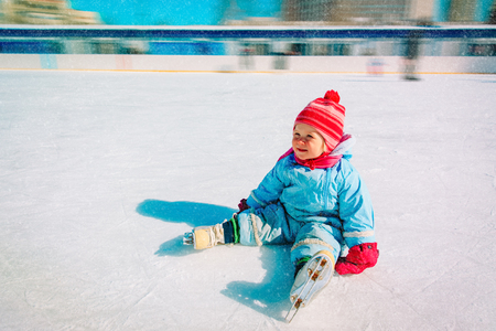 cute little girl sitting on ice with skates, learning skating Banco de Imagens - 109321403