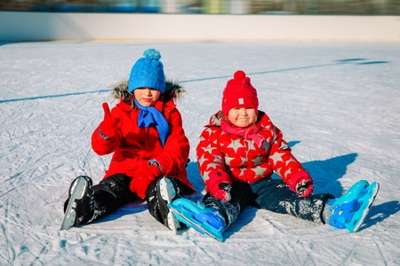 happy little boy and girl skating together