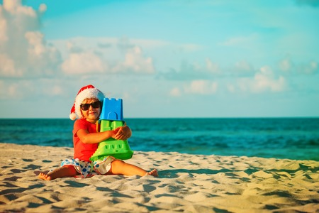happy little girl play with sand and toys on beach at christmas