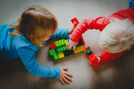 kids play with toy plastic blocks, learning concept Stock Photo