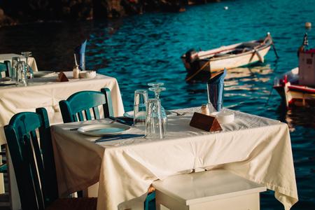 Greek taverna near the sea, cafe tables served