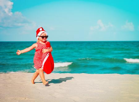 happy little girl play santa on tropical beach at christmas