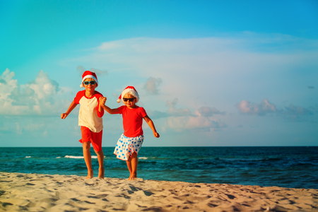happy kids-little boy and girl- celebrating christmas on beach Stock Photo