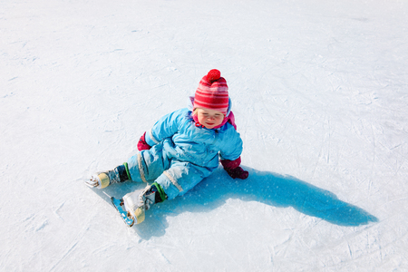 cute little girl sitting on ice with skates, learning skating
