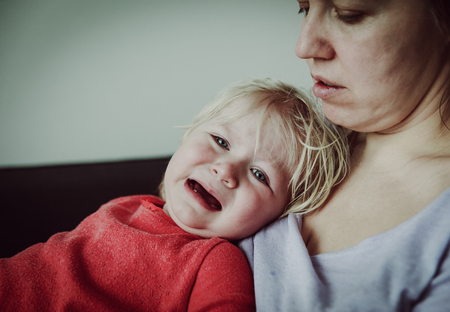 Mother comforting crying little baby, parenting concept Banco de Imagens