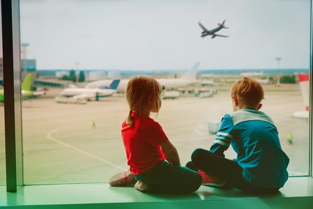 kids waiting for plane in airport, family travel Stock Photo