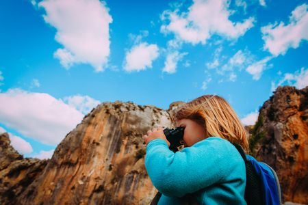 family travel- little girl with binoculars exploring nature Stock Photo