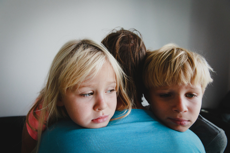 sad stressed little boy and girl hugging father, family in sorrow