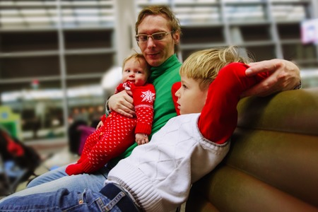 father with kids waiting in airport, family travel