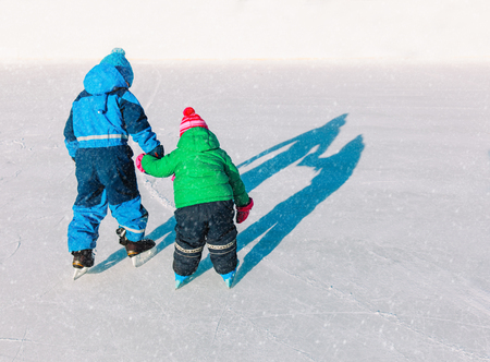 little brother teaching sister to skate in winter snow