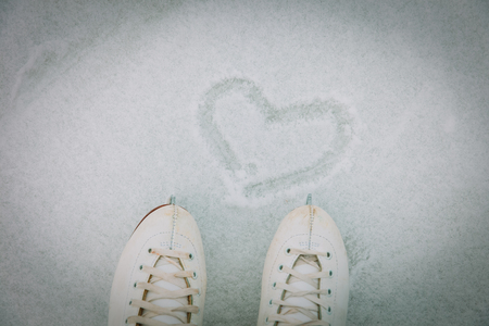 love skating concept - feet in skates and heart on snow