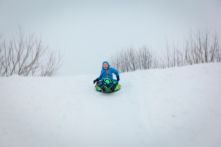 little boy enjoy winter slide, play in nature