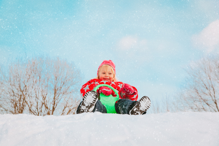 kids winter fun- little girl enjoy sliding in snow