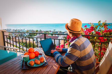 remote work concept- young man with laptop on scenic terrace 版權商用圖片