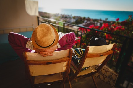 Dad and son relax on balcony terrace with sea view