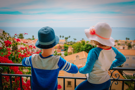 kids looking at city from balcony with sea view, family travel