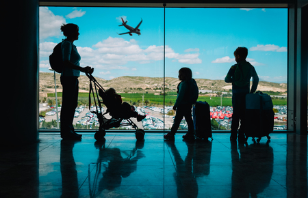 mother with kids and luggage looking at planes in airport Imagens