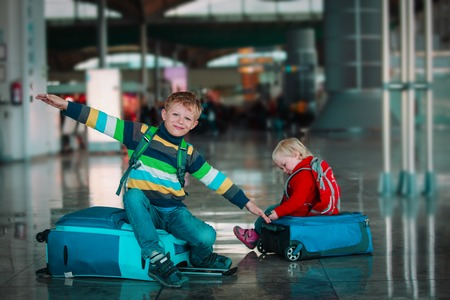 little boy and girl wait in airport, family travel